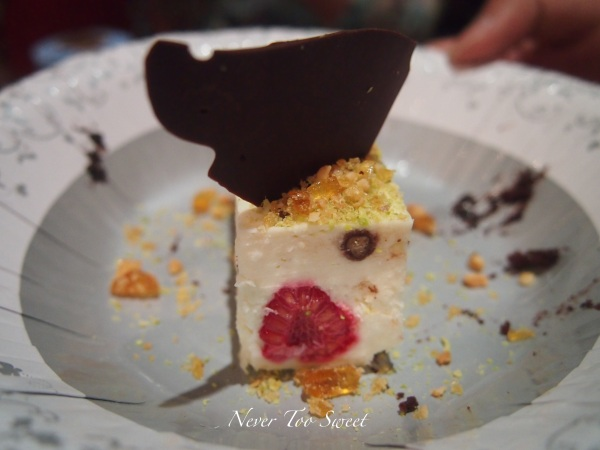 Raspberry and coconut seme fredo with pistachio praline topped with chocolate